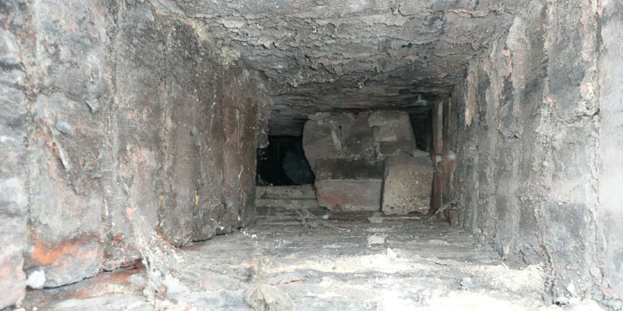 View down chimney showing loose bricks blocking it.